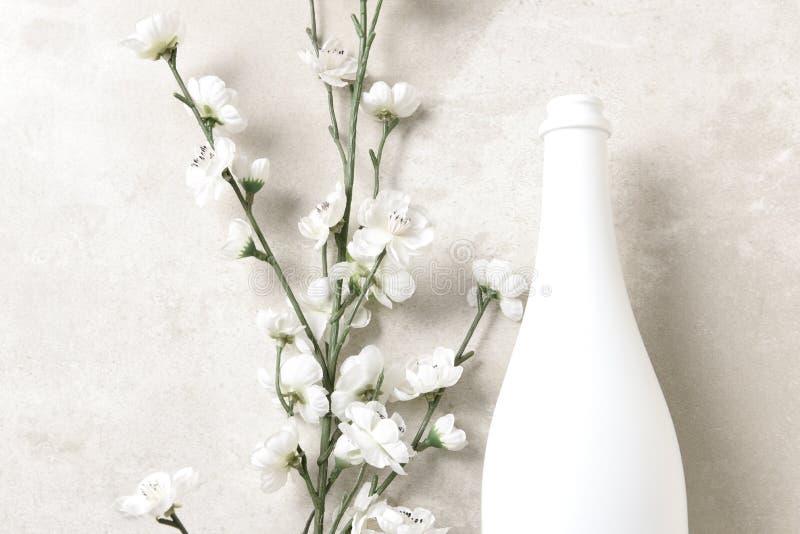 Fles met witte champagne en bloemen op een gevlekt lichtgrijs tafelblad Horizontaal met exemplaarruimte stock foto's