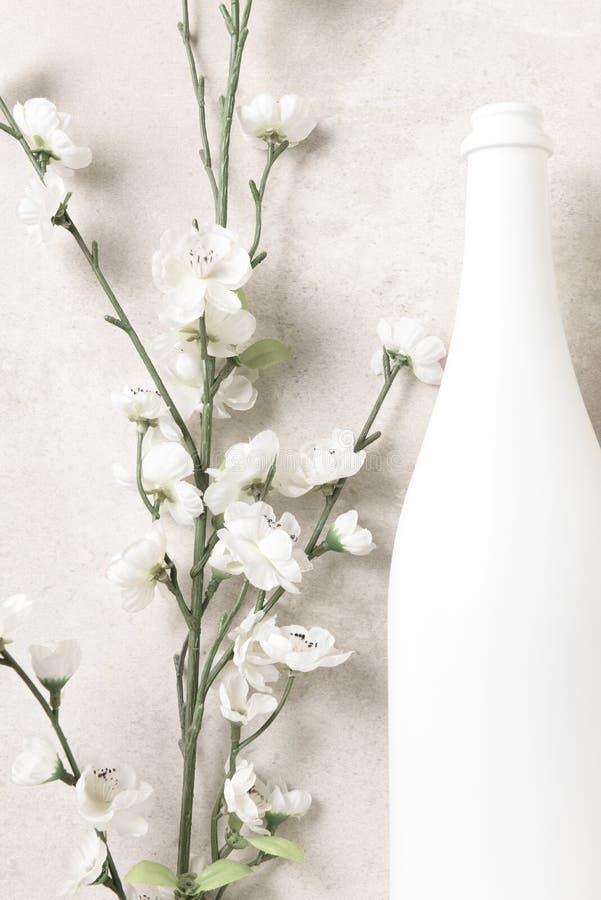 Fles met witte champagne en bloemen op een gevlekt lichtgrijs tafelblad Verticaal formaat stock fotografie