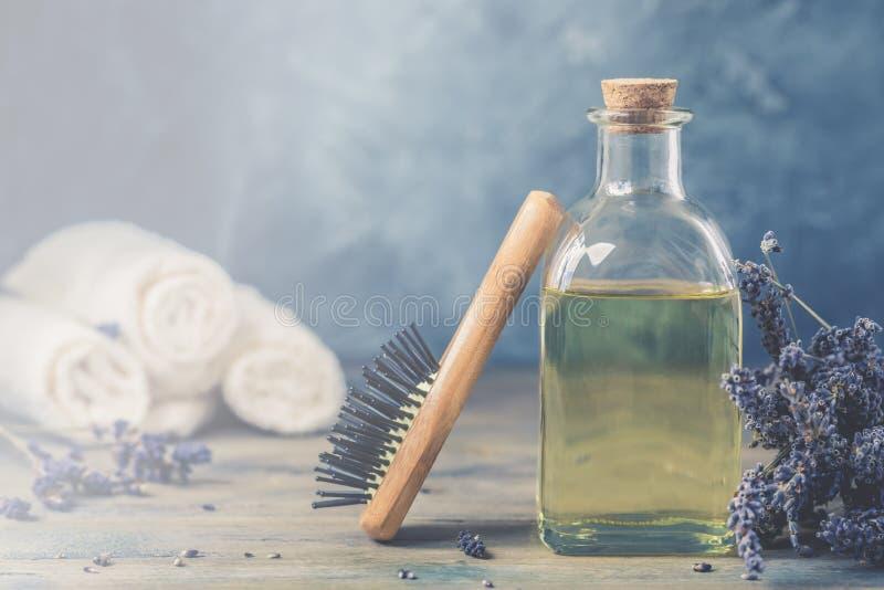 Fles natuurlijk kosmetisch lavendelolie, haar en lichaamsbehandeling, met een houten massagekam stock foto's