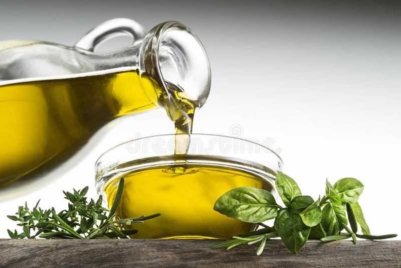 Fles olijfolie met kruiden die in glaskom gieten stock foto