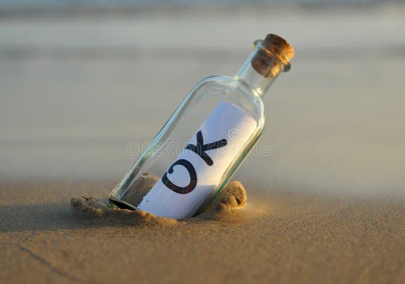 Fles op het strand met een bevestigend binnen antwoord, okey royalty-vrije stock afbeelding