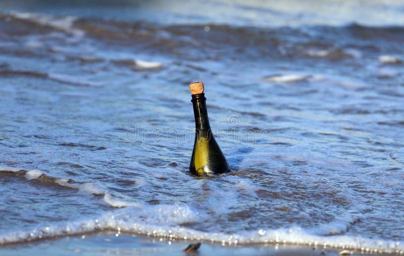 fles op het strand met een geheim bericht stock foto's