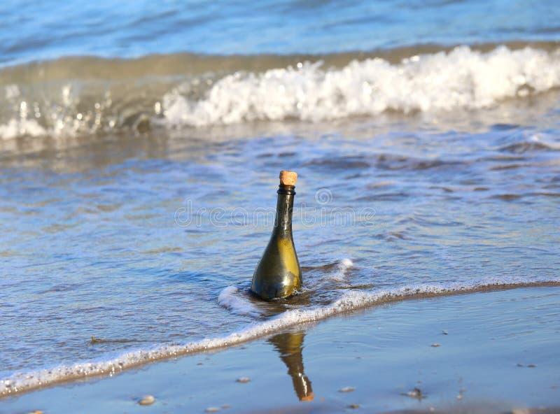 fles op het strand met een geheim bericht stock fotografie