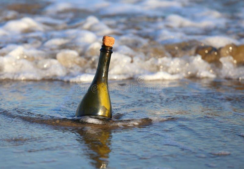 fles op het strand met een geheim bericht royalty-vrije stock fotografie