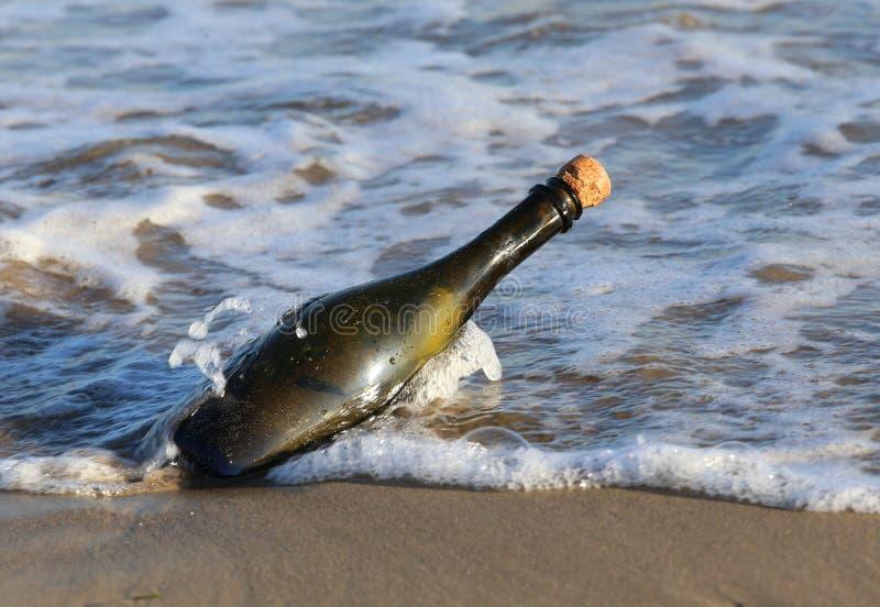fles op het strand met een geheim bericht stock afbeelding