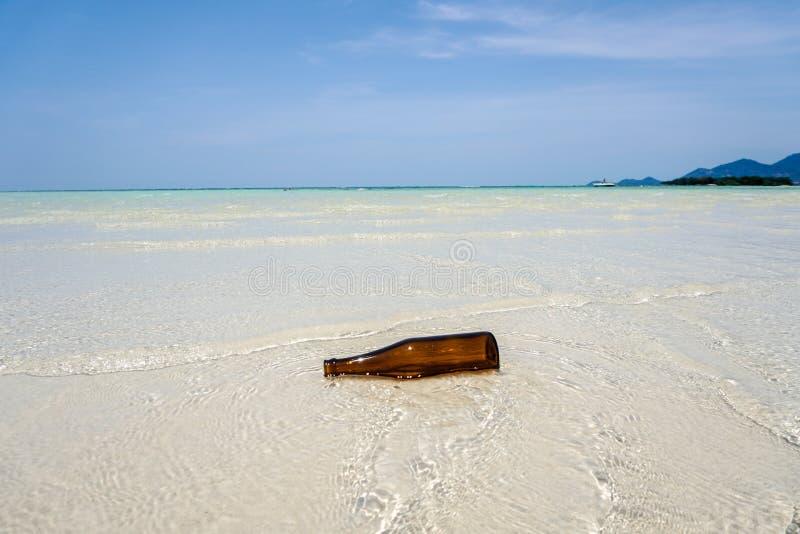 Fles op het strand wordt gelaten vallen dat stock afbeelding