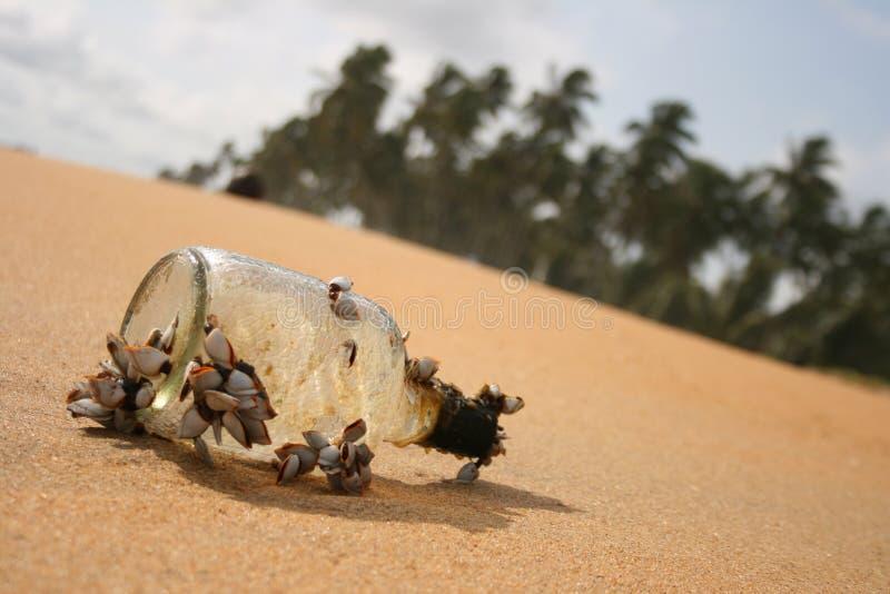 Fles op het zand royalty-vrije stock afbeelding