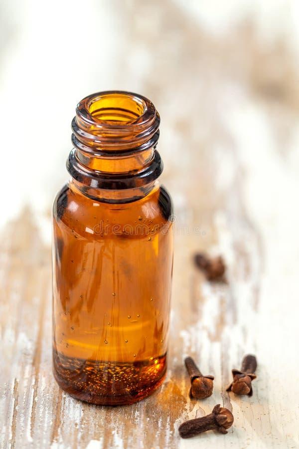 Fles Organische kruidnagelsetherische olie droog product dat op een houten achtergrond wordt uitgespreid stock fotografie