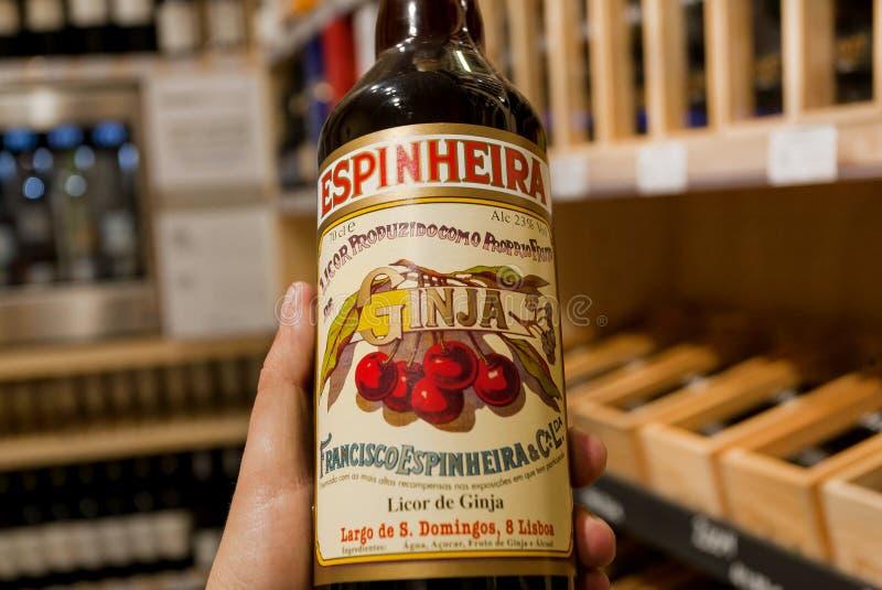 Fles populaire kersenalcoholische drank Ginja in de handen van de koper van een alcoholopslag stock foto