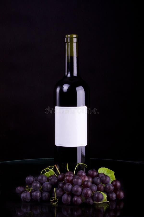Fles rode wijn en druiven ob zwarte achtergrond royalty-vrije stock afbeeldingen