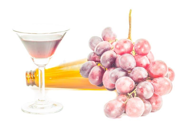 Fles rode wijn, en druiven op witte achtergrond stock foto's