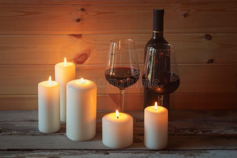 Fles rode wijn, glazen rode wijn en kaarsen op oude houten lijst royalty-vrije stock afbeelding