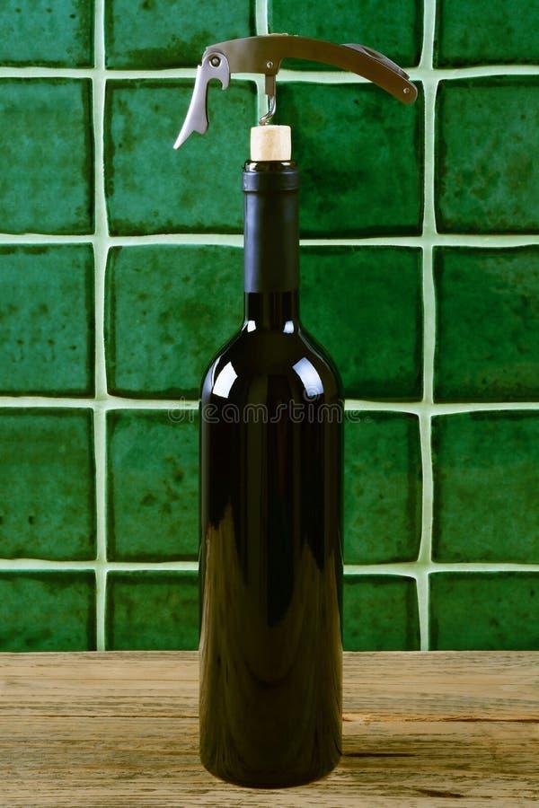 Fles rode wijn met kurketrekker over groene achtergrond royalty-vrije stock foto