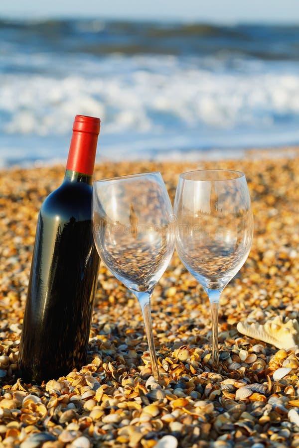 Fles rode wijn met wijnglas twee op het strand royalty-vrije stock afbeeldingen