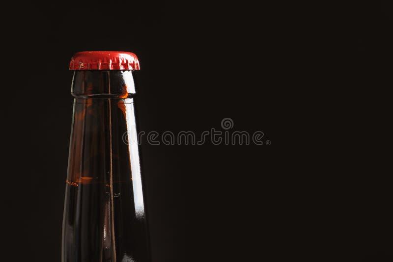 Fles smakelijk koud bier op zwarte achtergrond stock afbeelding