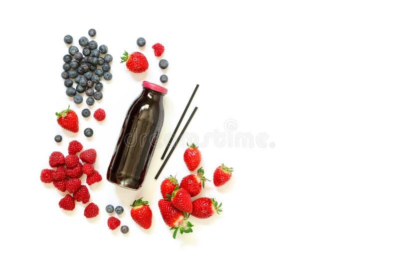 Fles van aardbeien, frambozen, bosbessensap op wit wordt geïsoleerd dat stock afbeelding