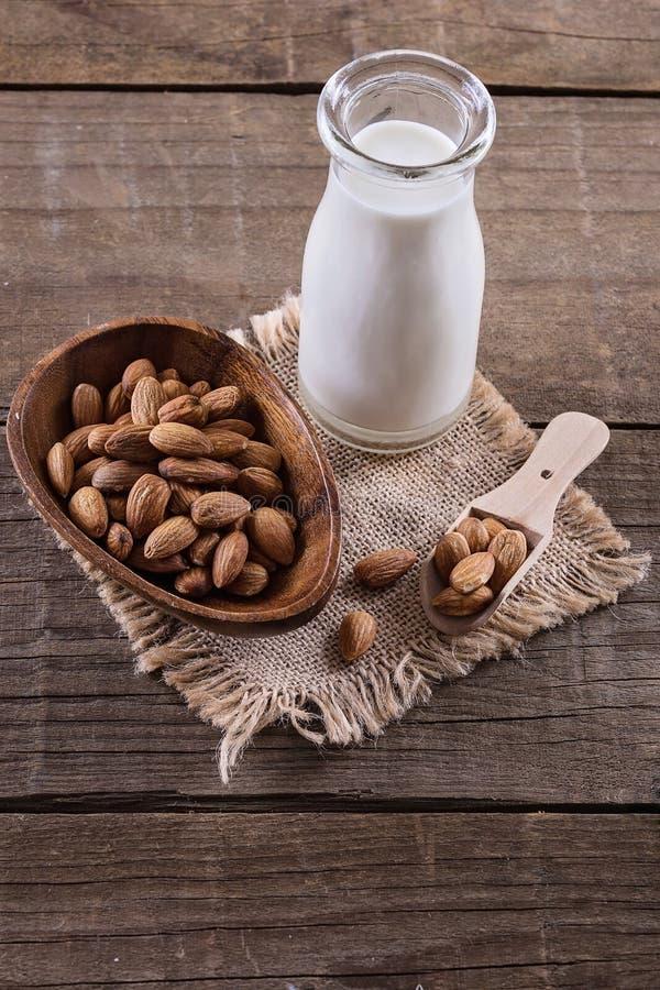 Fles van amandelmelk en noten over rustieke houten achtergrond stock foto's