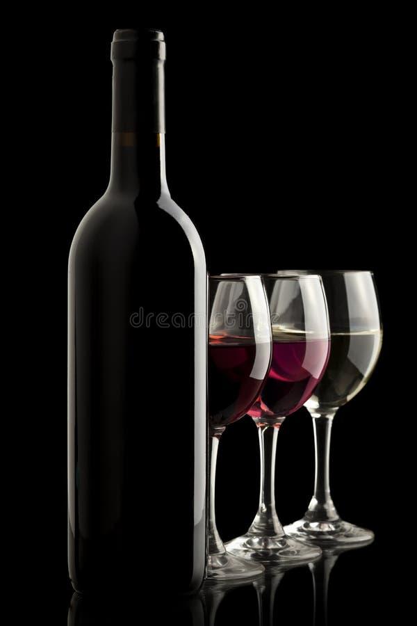 Fles van de wijn met rood, wit en nam wijnglazen toe stock foto's