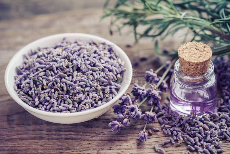 Fles van etherische olie en lavendelbloemen in kom royalty-vrije stock afbeelding
