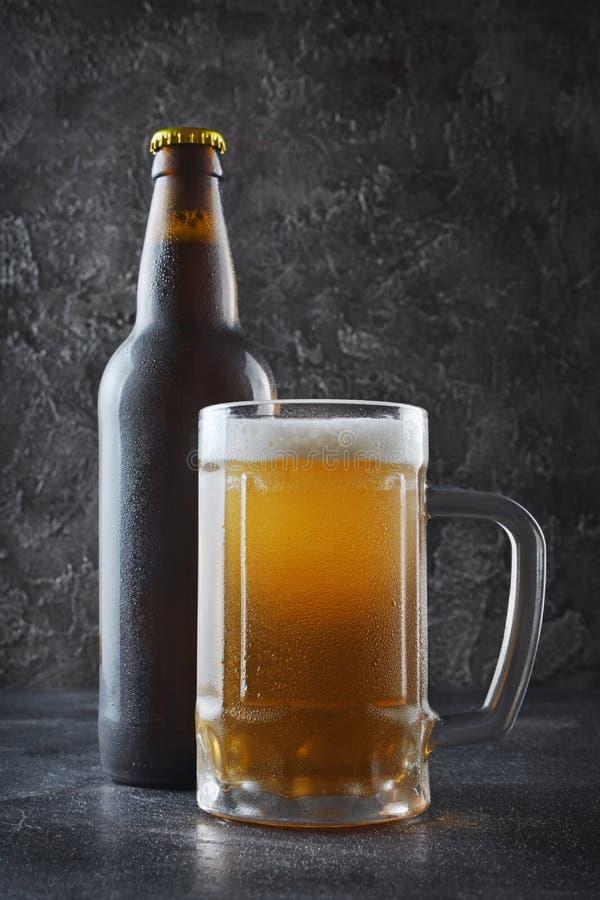 Fles van koude bier en glasmok met schuim royalty-vrije stock foto