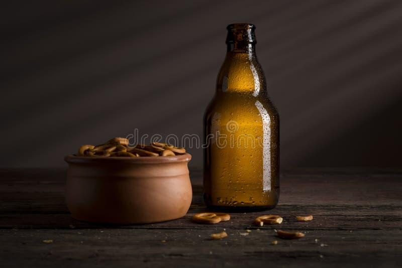 Fles van koude bier en pretzels stock afbeeldingen