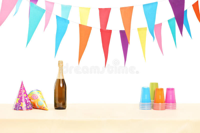 Fles van mousserende wijn, plastic glazen en partijhoeden stock foto