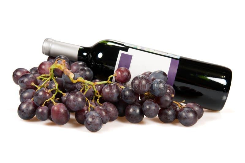 Fles van rode wijn en druiven stock fotografie
