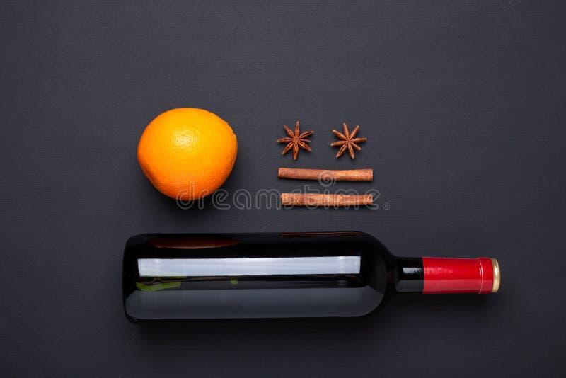 Fles van rode wijn en kruid voor overwogen wijn op zwarte achtergrond Kaneel, anijsplantsterren, sinaasappel stock afbeelding