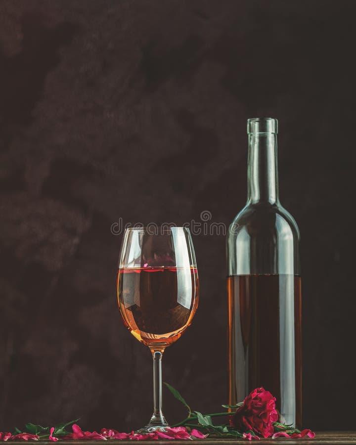 Fles van roze wijn en glas dat wordt geserveerd met roze wijn en roze petjes, roze roze roze roze roze op een donkere achtergrond royalty-vrije stock foto's