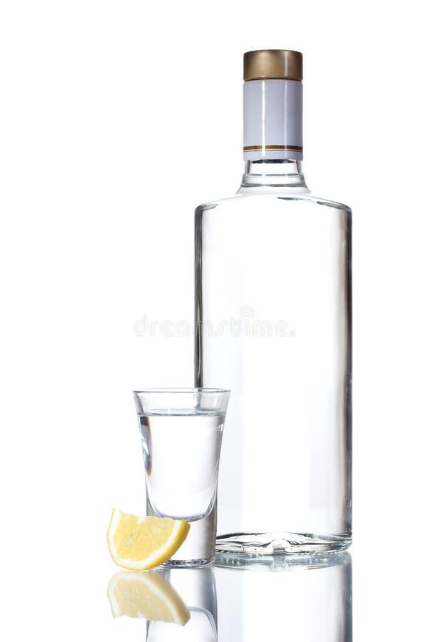 Fles van wodka en wijnglas met citroen stock afbeeldingen