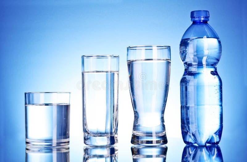 Fles water en glas op blauw stock afbeeldingen