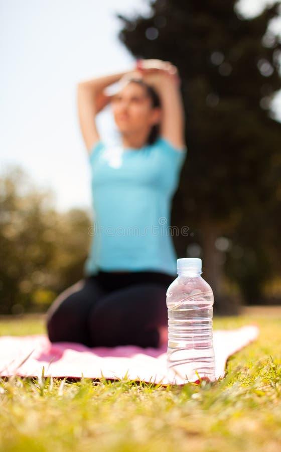 Fles water met zich vrouw het uitrekken op achtergrond stock foto