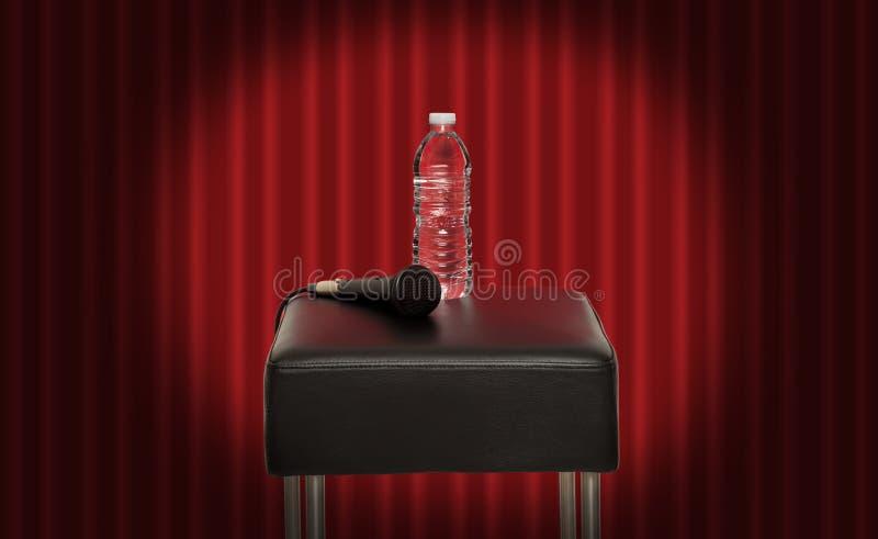 Fles water naast een microfoon royalty-vrije stock afbeeldingen