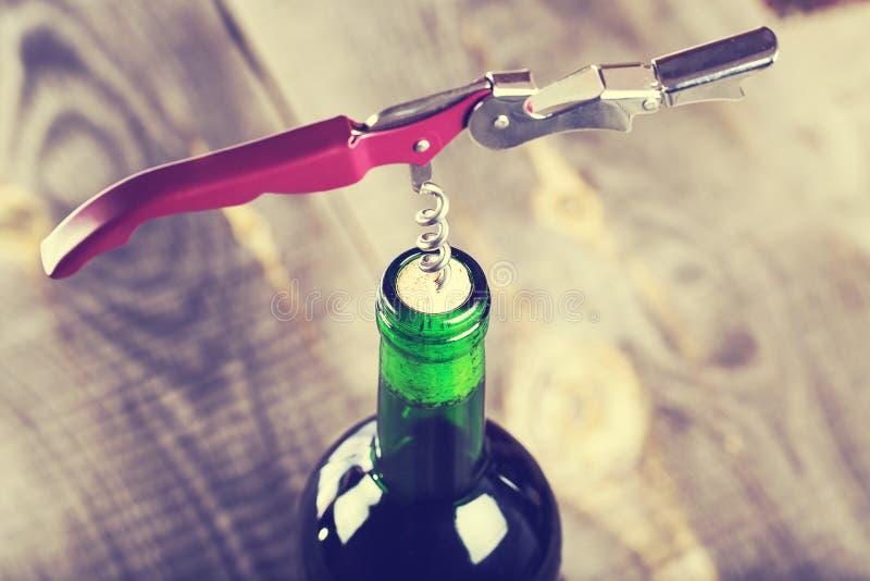 Fles wijn met kurketrekker stock foto's