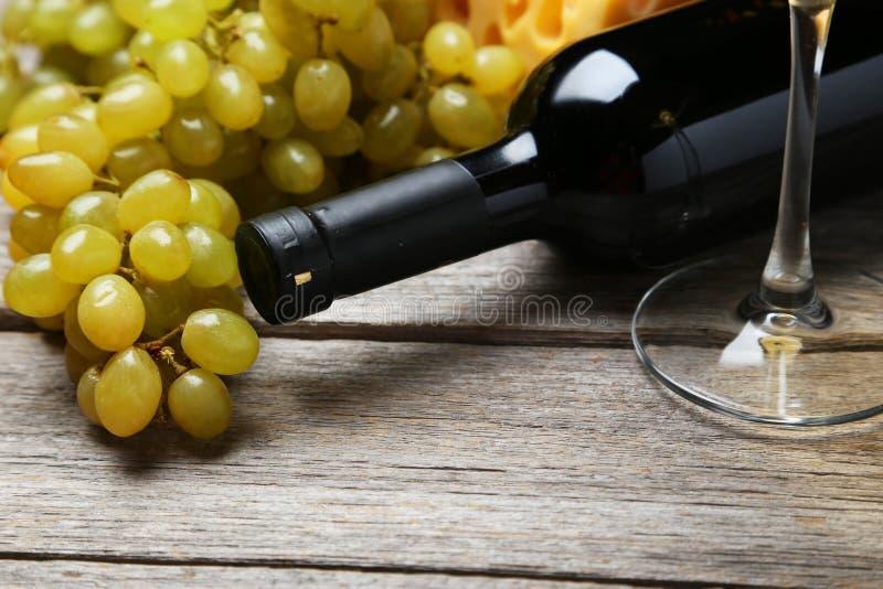 Fles witte wijn met druiven op de grijze houten achtergrond stock foto