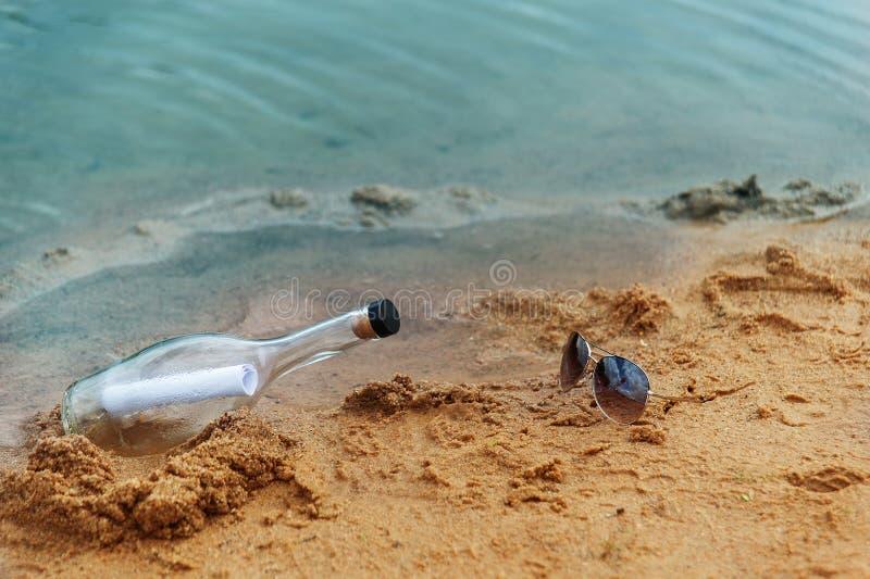 Fles in zand stock foto