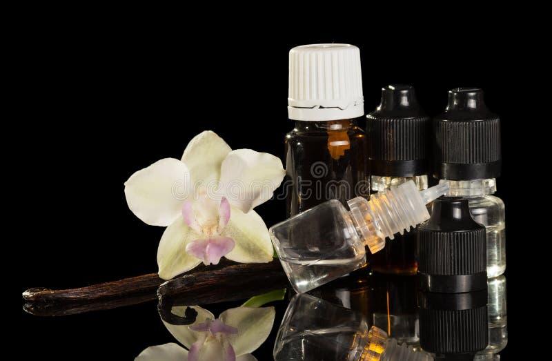 Flessen aromatische vloeistof voor vaping, vanillepeulen en Orchideebloem geïsoleerd op zwarte royalty-vrije stock afbeelding