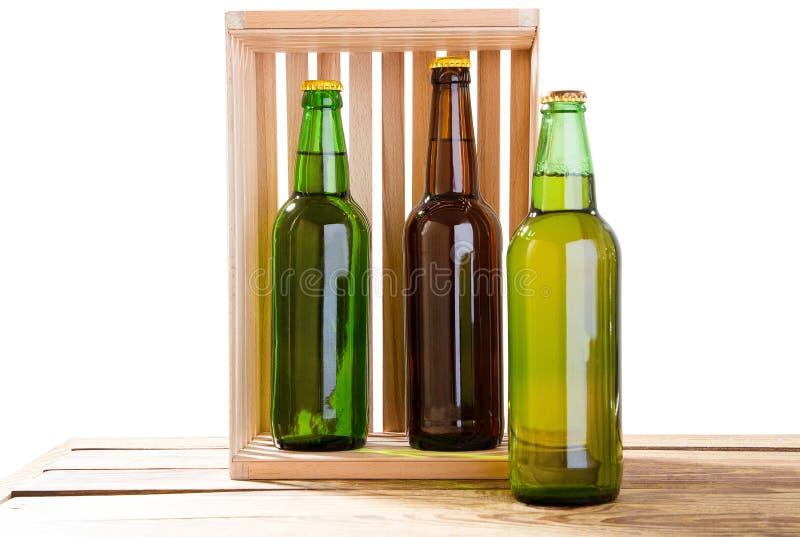 Flessen bier op houten die lijst op witte achtergrond, de spot van glasflessen omhoog wordt geïsoleerd, verschillende bierflessen stock foto's