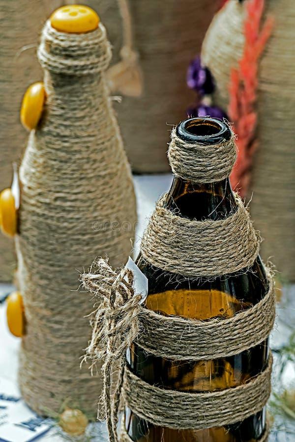 Flessen die met vlaskabel worden gevlecht stock foto's