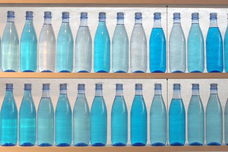 Flessen die met water worden gevuld, dat zich op de plank bevindt royalty-vrije stock afbeelding