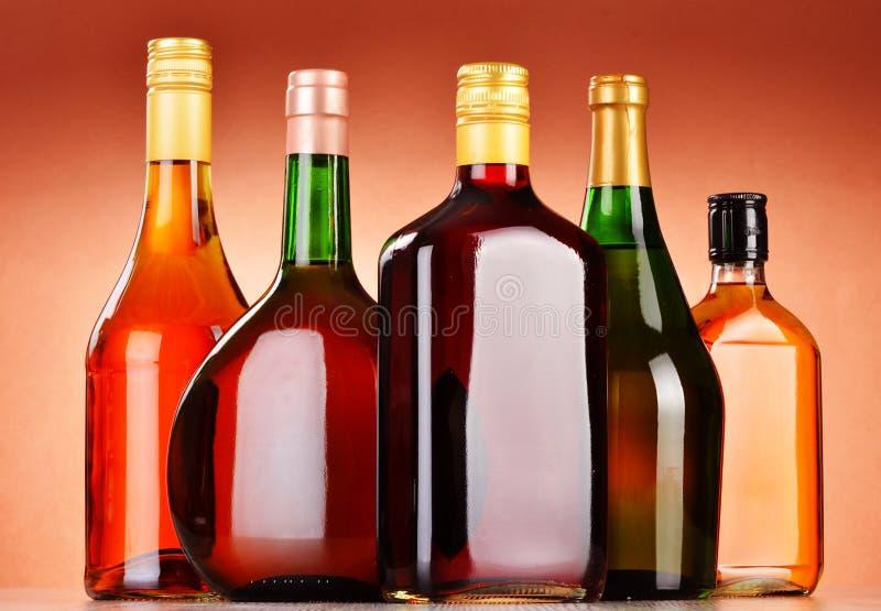 Flessen het geassorteerde alcoholische dranken omvatten en wijn stock foto