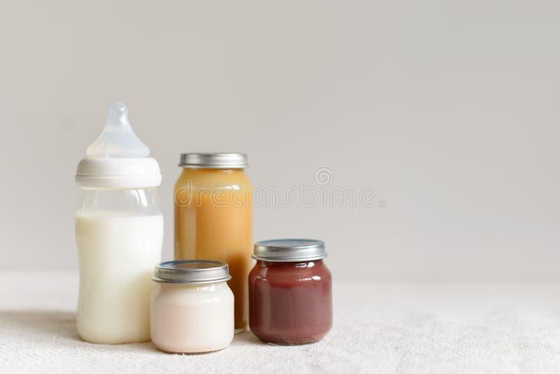 Flessen melk en puree voor baby over vage achtergrond stock foto