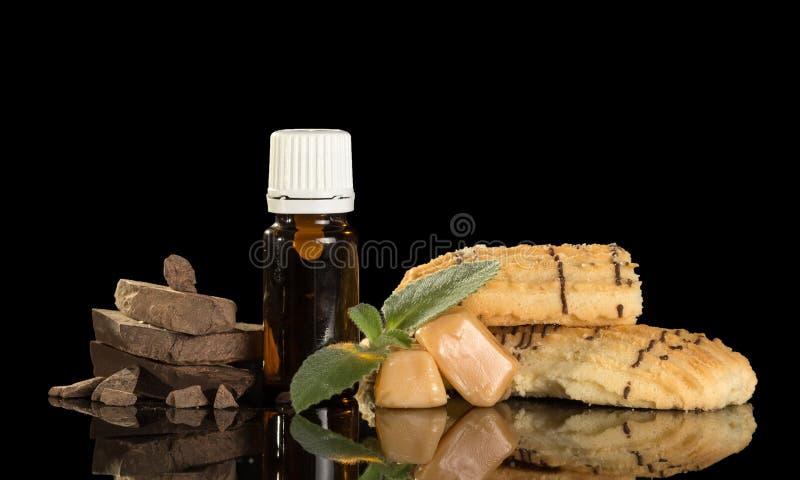 Flessen met aromatische vloeistof voor het roken, koekjes en chocolade royalty-vrije stock afbeelding