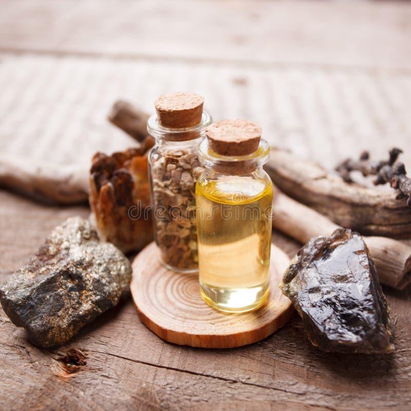 Flessen met kruiden, droge bloemen, stenen en magische voorwerpen op heksen houten lijst stock afbeelding