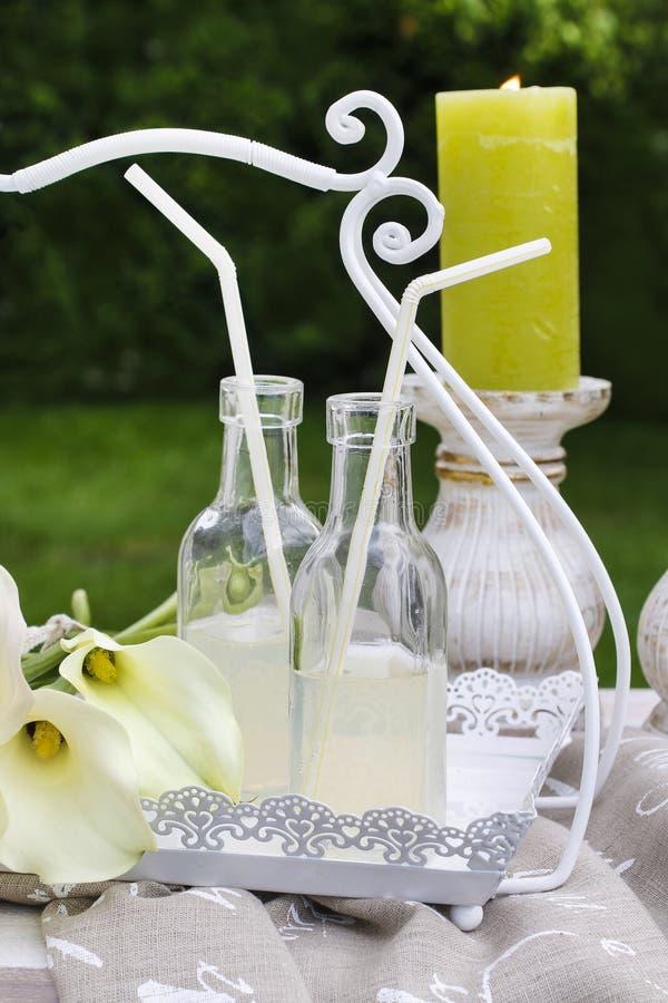 Flessen met limonade en calla bloemen in de tuin stock fotografie