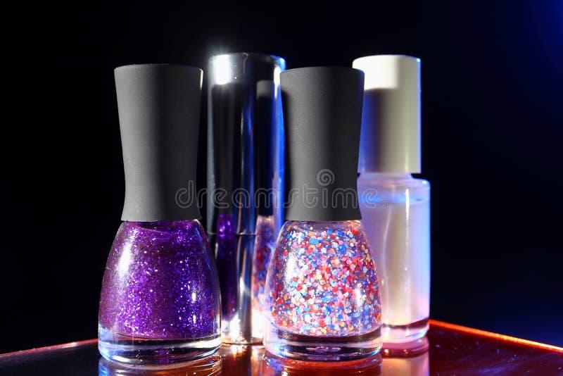 Download Flessen Met Nagellak Op Zwarte Achtergrond Stock Foto - Afbeelding bestaande uit stroom, blauw: 114227328