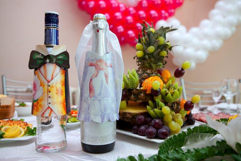 Flessen met wijn op een huwelijkslijst stock foto's