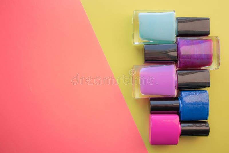 Flessen nagellak Een groep heldere manicures op een roze, gele achtergrond Met lege ruimte op de linkerzijde stock afbeelding