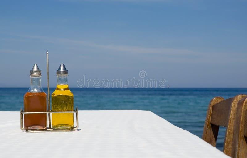 Flessen olijfolie en azijn op lijst dichtbij overzees stock afbeeldingen
