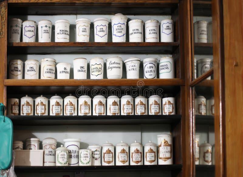 Flessen op de plank van oude apotheek stock foto's